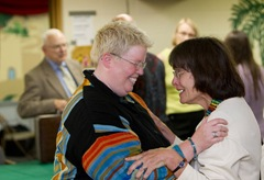 The Rev. Amy DeLong (left, foreground) is congratulated by supporter Rebecca Neal Niese (right) at the conclusion of her church trial at Peace United Methodist Church in Kaukauna, Wis. At left rear is Bishop Clay Foster Lee Jr.,  who served as presiding officer for the trial.  A UMNS photo by Mike DuBose.